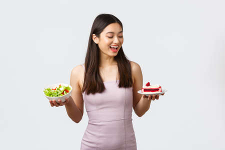 Healthy lifestyle, leisure and food concept. Cheerful beautiful asian girl in dress, looking excited with happy smile at cake instead of bowl with salad, standing white background