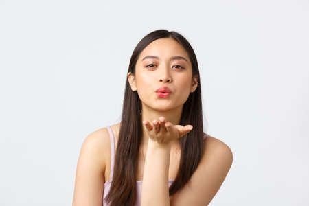 Beauty, fashion and people emotions concept. Close-up portrait of romantic, coquettish beautiful girl in dress, sending air kiss at camera with palm, standing white background