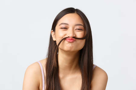 Concept of beauty, fashion and makeup products advertisement. Close-up portrait of happy silly asian girl making fake moustache out of hair strand, smiling cheerful, white background