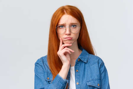 Uneasy, indecisive timid cute redhead girl dont know what do in future, deciding what college enter, having troubled with making choice, pouting and looking camera gloomy