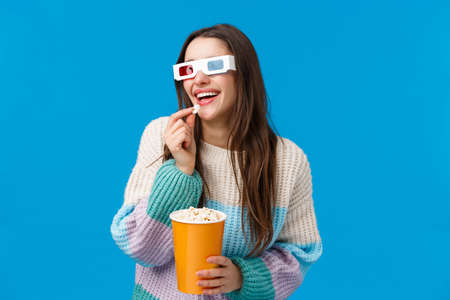 Leisure, fun and people concept. Attractive happy smiling brunette, female student in sweater and 3d glasses, laughing out loud over funny 3d movie, wear glasses and eat popcorn, blue background