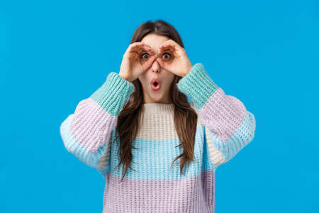 Girl found amazing, stunning offer. Amazed speechless and astounded young attractive woman holding hands like binocular over eye, folding lips excited, popping eyse camera impressed, see good promo