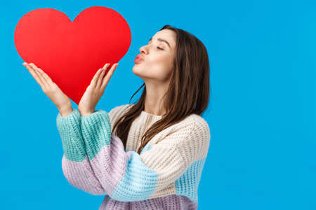 Dreamy young woman cherish her relationship, prepare valentines day gift, kissing big cute red heart sign over left side copy space, standing blue background delighted and upbeat 免版税图像