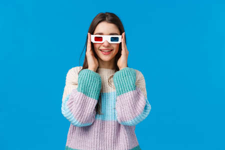 Turn on, lets start. Attractive amused and happy smiling young woman in winter sweater, wear 3d glasses and grinning, tempt see new premiere in cinema, watching movie over blue background