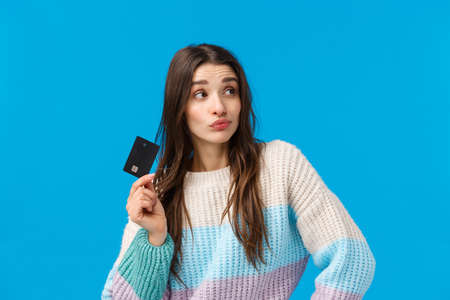 Shopping, winter holidays and women concept. Curious and thoughtful good-looking stylish woman thinking how waist all money, holding credit card, pouting and pondering, blue background