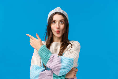 Wow its interesting, lets see. Intrigued and excited cute smiling woman in winter sweater, hat, folding lips curiously pointing finger left, telling about awesome event, standing blue background