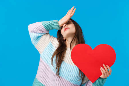 Passion, feelings and romance on valentines day concept. Passionate tender attractive woman in love, losing her mind over love, fain and hold hand on forehead, holding cute red heart sign