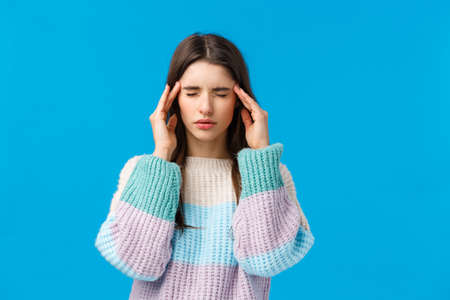 Hungover, health and people concept. Stressed young woman feeling headache, close eyes touching temples, trying easy pain with medicine, suffering migraine, standing blue background Stock Photo
