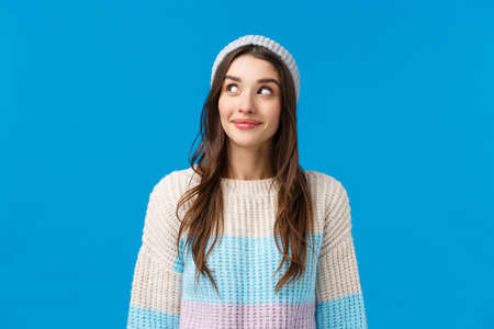 Girl curious what happening over corner, peeking and smiling excited, want see something interesting going on, standing blue background upbeat with lovely grin, wear winter sweater and hat