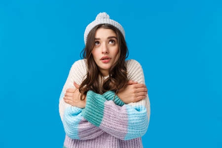 Girl watching at snowflakes, looking up and trembling from cold standing in winter hat, sweater, hugging herself to warm-up, embracing body clench teeth freezing temprature, blue background