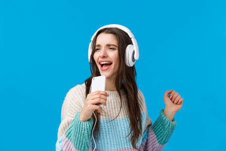 Waist-up portrait carefree good-looking young brunette woman playing karaoke game on phone, holding smartphone like mic, singing into phone dancing, listen music in headphones, blue background 免版税图像