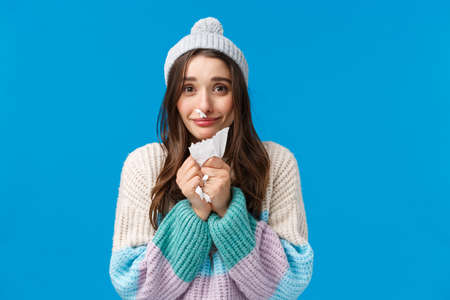 Silly and cute lovely, smiling brunette girl in winter sweater, hat, have runny nose, caught cold on winter holidays, apologizing for sneezing, holding napkin, standing blue background 免版税图像