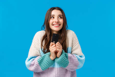 Dreamy and upbeat, thoughtful young woman dreaming how she will spend all money cashback, placed cash deposit to save-up, holding credit card, imaging something lovely, smiling