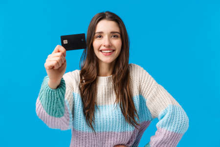 Best bank for young generation. Attractive pleased charismatic young woman in winter sweater, showing credit card and smiling satisfied, recommend financial system, new banking features
