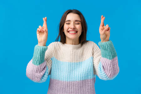 Optimistic cute feminine young girl in winter sweater, having faith dreams do come true, smiling broadly, close eyes making wish with fingers crossed for good luck, praying, blue background 免版税图像