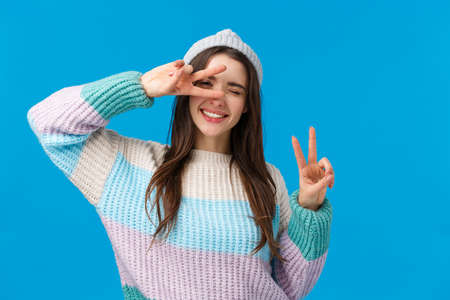 Pack your things and travel. Joyful and carefree upbeat smiling woman, wear winter sweater and hat, wink camera and make peace signs, tilt head, enjoying beautiful, amazing vacation, blue background