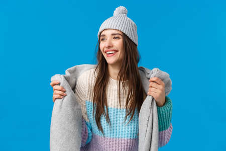Attractive and carefree, dreamy pretty woman with long dark hair, wearing winter hat, sweater, wrapping scarf around neck going outside, ski and enjoying christmas holidays, look away smiling