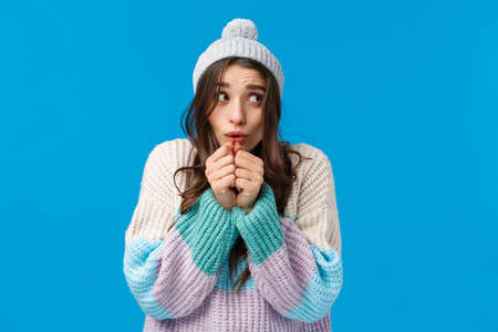 Silly cute, lovely young woman in winter hat, sweater, shaking from cold, blowing hot air at hands to warm-up after playing snowballs outdoors, standing innocent and tender over blue background