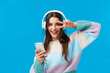 Happy sassy good-looking brunette woman in headphones, winter sweater, enjoying favorite songs in new earphones, show peace, disco gesture holding smartphone, smiling camera pleased