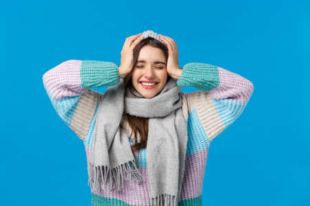Cant believe dreams do come true, christmas miracle, new year concept. Attractive cheerful brunette woman in winter sweater, scarf and jat, close eyes dreamy and smiling, cheering blue background 免版税图像