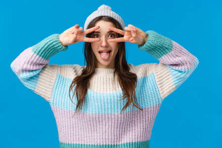 Be yourself. Attractive and playful funny, beautiful caucasian girl in winter hat, sweater, showing tongue and make disco, peace signs over eyes, having fun on christmas holidays, blue background 免版税图像