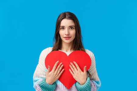 Sensual, romantic and attractive brunette woman embracing big red heart card and looking camera flirty, receiving valentines day symapthy confession, feeling love and care, standing blue background 免版税图像