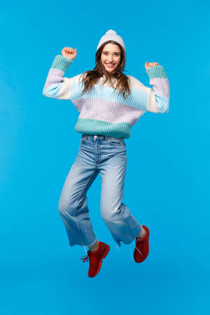 Vertical full-length portrait super happy girl jumping from amazement, celebrating new year, christmas party, enjoying holidays, shopping with awesome big discounts, smiling upbeat, blue background