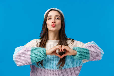 Showing her love. Pretty sensual and cute, coquttish brunette woman in winter sweater, hat, blowing air kiss, folding lips silly and showing heart gesture over chest, show affection and passion 免版税图像