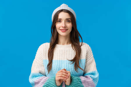 Pretty, lovely and tender feminine young brunette girl with long hair, wear winter hat and sweater, hold hands together and smiling cute, looking with admiration, standing blue background happy