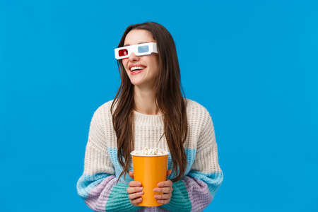 Waist-up portrait happy, cheerful and relaxed modern young female student watching movie on big screen in 3d glasses, winter sweater, look aside laughing over comedy, funny film, eat popcorn