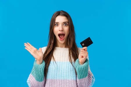Surprised and amazed girl received bonus on bank account, raise hand up holding credit card, yelling from amazement and happiness, got lots money, wasting saving for holidays gifts, blue background