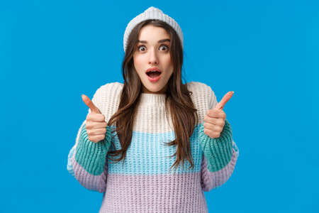 Surprised and happy amazed young brunette woman in winter hat, sweater, stare camera impressed, gasping hold breath speechless staring awesome thing and show thumbs-up in like, yes gesture 免版税图像