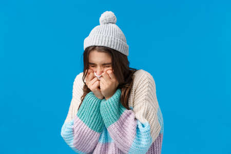 Cold, flu health concept. Silly pretty brunette woman in winter hat, sweater, squinting sneeze at napkin, feeling unwell have runny nose, disease symptoms, standing blue background 免版税图像
