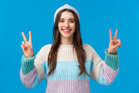 Happy and carefree cute, charismatic brunette female in winter sweater, hat, showing two peace signs and smiling broadly, photographing on winter holidays, mountain ski luxury resort, blue background