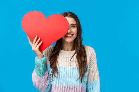 Valentines day, romance and relationship concept. Cheerful lovely brunette woman prepared cute gift for girlfriend, holding big red cardboard heart near face and grinning joyfully, blue background 免版税图像