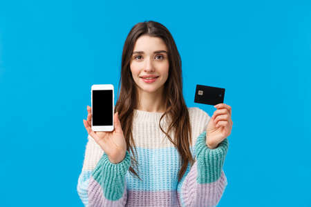 Waist-up portrait assertive young woman smiling, showing how banking system works, connect bank account with smartphone application, holding credit card and mobile, showing something on display