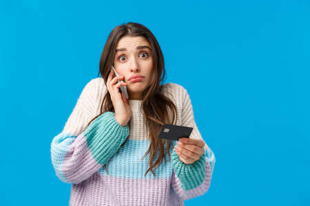 Gloomy and indecisive confused cute girl calling bank service cant understand where all money go during winter holidays shopping season, talking on phone, holding credit card, blue background 免版税图像