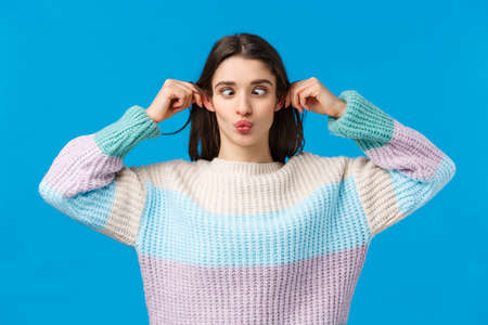 Funny and playful girl making goofy faces, squinting folding lips and pulling ears as mimicking, having fun, joking around, copying someone, standing blue background joyful and carefree