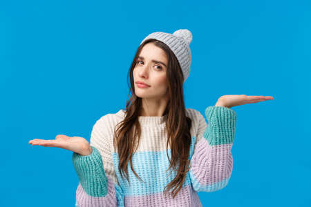 Girl troubled make choice, finally decided what buy, holding hands raised like weighing products, looking camera thoughtful, indecisive, asking help with picking winter holidays gift, blue background