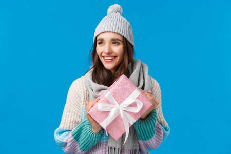 Holidays, christmas and valentines day concept. Romantic attractive young girlfriend 20s in scarf, winter hat and sweater, holding cute pink wrapped gift, prepared present for friend, smiling happy