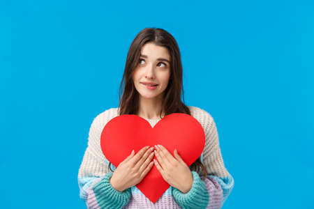 Dreamy lovely and shy, thoughtful attractive woman want give valentines day heart cardboard to express sympathy, confess love and affection, dreamy looking up, biting lip tempting, blue background 免版税图像