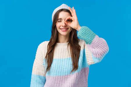 Waist-up portrait cheerful beautiful brunette woman in winter sweater, hat, showing okay, good gesture, OK sign over eye, smiling and wink in approval, assertive everything alright, blue background