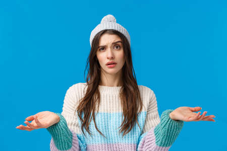 Waist-up portrait confused young attractive woman in winter sweater, hat, cant understand, standing clueless and uncertain, shrugging raise hands up dismay, dont know answer, blue background
