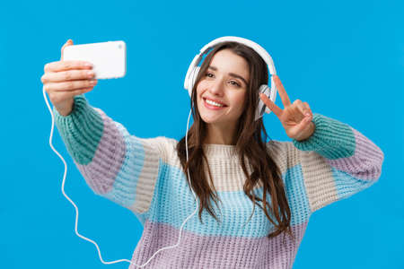 Waist-up portrait cute and tender, lovely charismatic woman taking selfie on smartphone, wearing headphones, listen music, posing with peace gesture as trying-out new app filters for photo