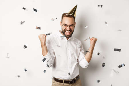 Celebration and holidays. Happy man dancing on birthday party with confetti, wearing b-day hat and rejoicing, standing over white background Reklamní fotografie