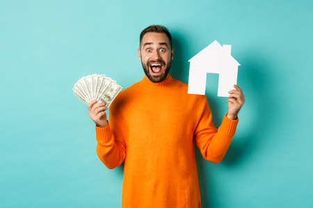 Real estate concept and mortgage concept. Excited man showing dollars and paper maket of house, buying flat, standing over blue background