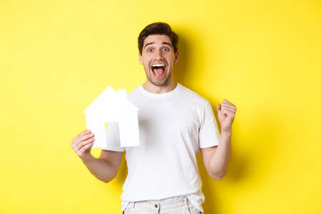 Real estate concept. Excited man holding paper house model and celebrating, standing happy over yellow background