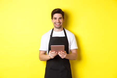 Waiter in black apron taking orders, holding digital tablet and smiling friendly, standing over yellow background