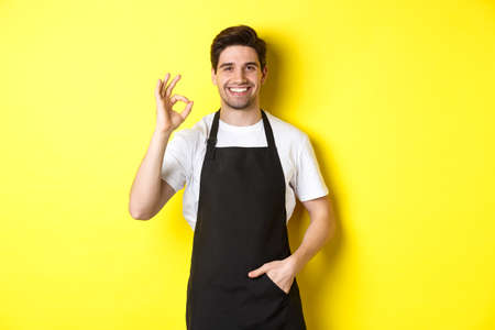 Young smiling barista in black apron showing okay sign, recommending coffee shop or restaurant, standing over yellow background Standard-Bild