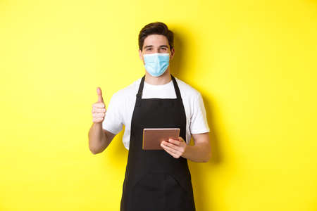 Concept of covid-19, small business and pandemic. Friendly waiter in medical mask and black apron showing thumb up, taking orders with digital tablet, yellow background